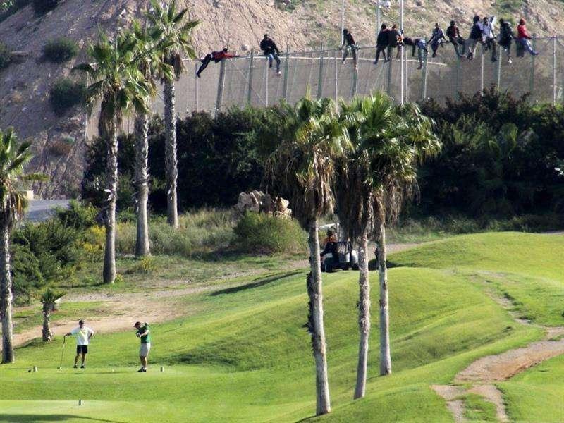 Varias personas juegan al golf en un campo de Melilla ante los inmigrantes de origen subsahariano. Foto: EFE en español