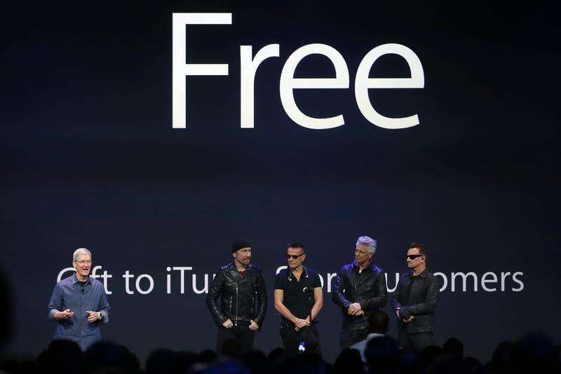 Apple CEO Tim Cook (L) stands with Irish rock band U2 as he speaks during an Apple event announcing the iPhone 6 and the Apple Watch at the Flint Center in Cupertino, California, September 9, 2014. Foto: Stephen Lam/Reuters