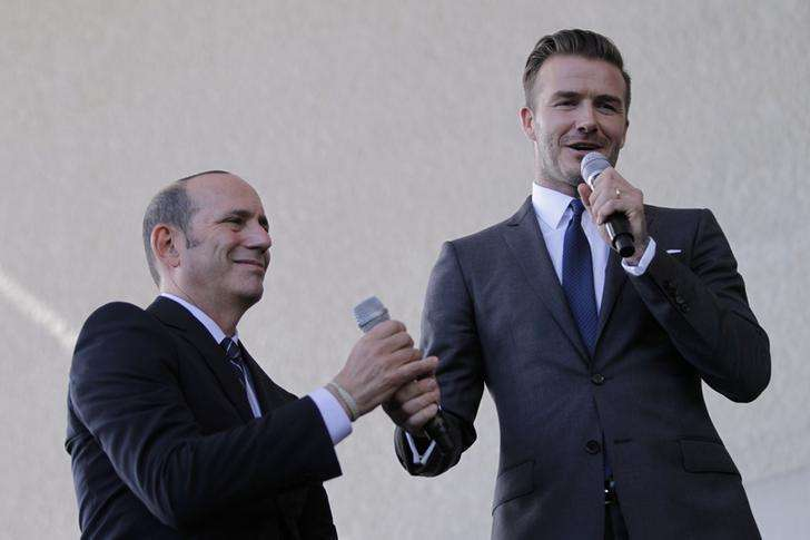 Don Garber (L), Major League Soccer (MLS) commissioner, exchanges working microphones with David Beckham at a news conference in Miami, Florida February, 5, 2014. Foto: Andrew Innerarity/Reuters