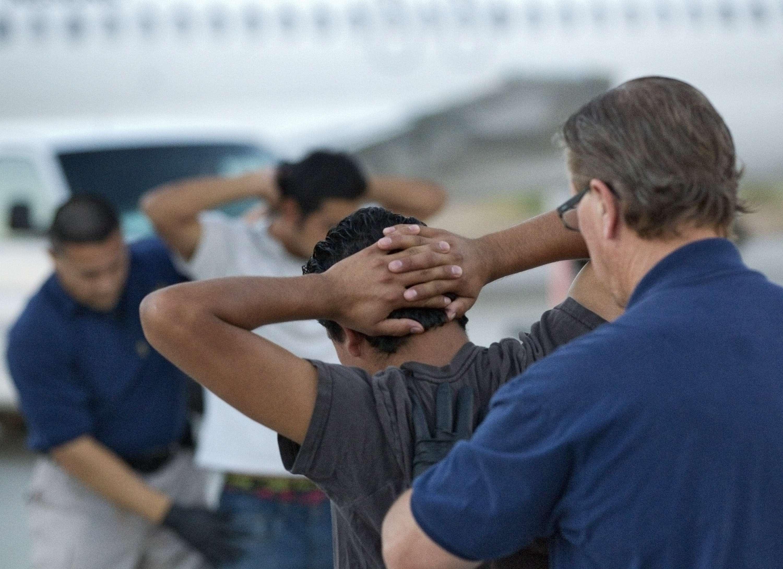 Un grupo de salvadoreños son preparados por agentes policiales para su deportación. Foto: AP en español