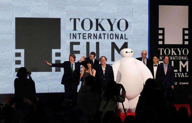 "Directors of ""Big Hero 6 "" Don Hall (L) and Chris Williams (3rd L) wave with Japanese actress Miho Kannno (2nd L) as Chief Creative Officer of Pixar and Walt Disney Animation Studios, John Lasseter (4th L), and the producer Roy Conli (3rd R), Japanese actor and son of former Prime Minister Junichiro Koizumi, Kotaro Koizumi (2nd R), and Disney Animation Studio Executive Vice President Andrew Millstein (R) attend the opening event of the Tokyo International Film Festival before the world premiere of their film ""Big Hero 6 "" in Tokyo October 23, 2014. Foto: Yuya Shino/Reuters"