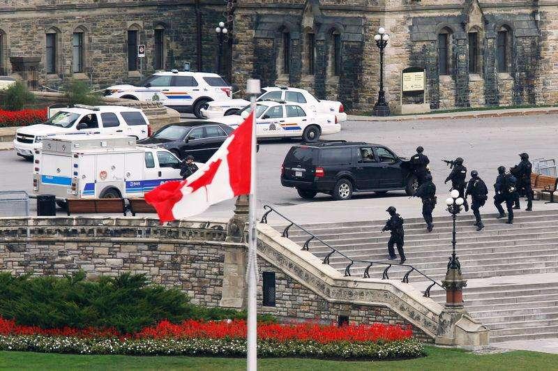 Policiais armados se aproximam do bloco central do Parlamento após um tiroteio, em Ottawa, no Canadá, nesta quarta-feira. 22/10/2014 Foto: Chris Wattie/Reuters
