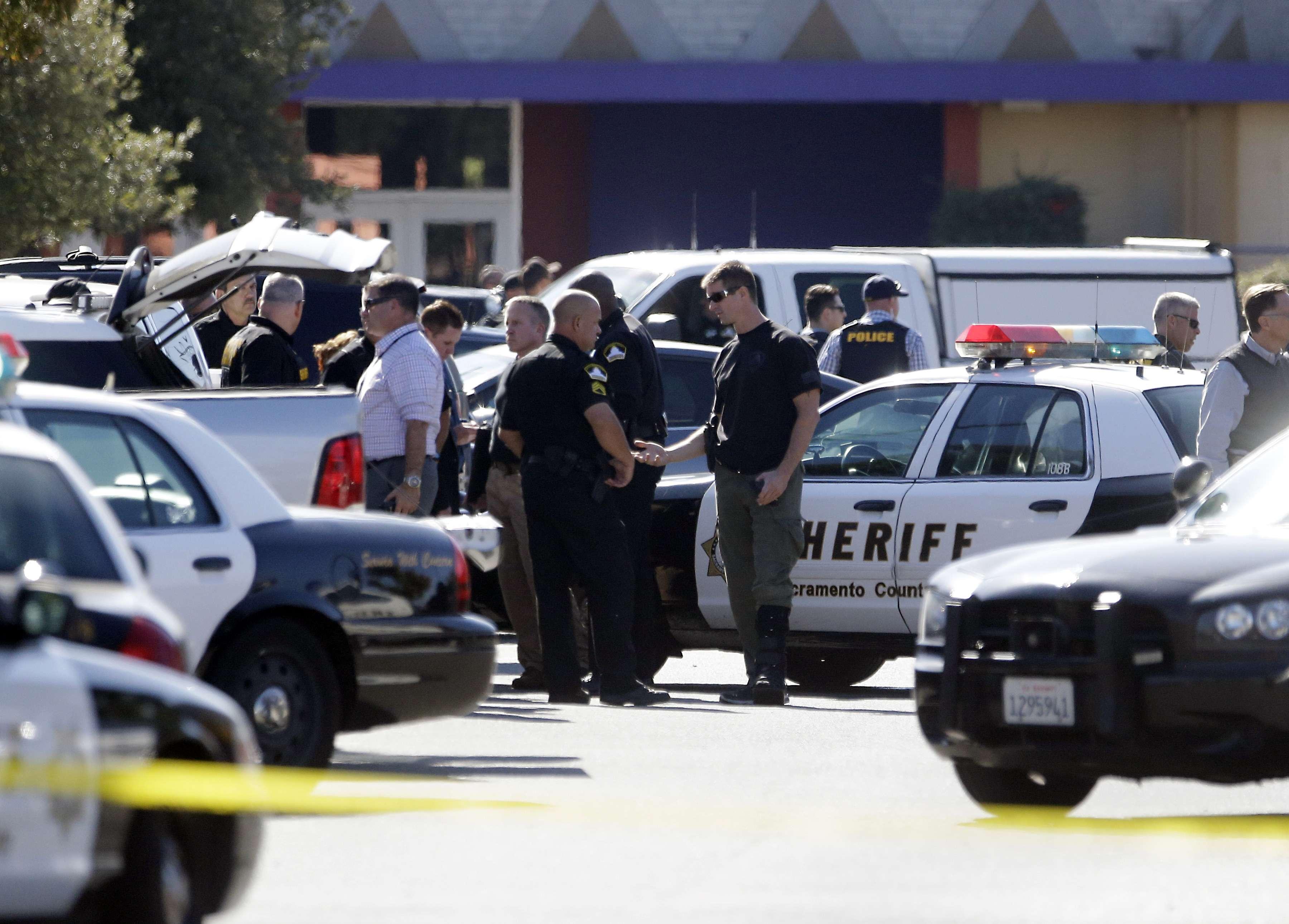 Varios policías se reúnen en el sitio donde un agente del condado de Sacramento fue baleado por un agresor que luego secuestró dos vehículos en Sacramento, California, el viernes 24 de octubre de 2014. Foto: AP en español