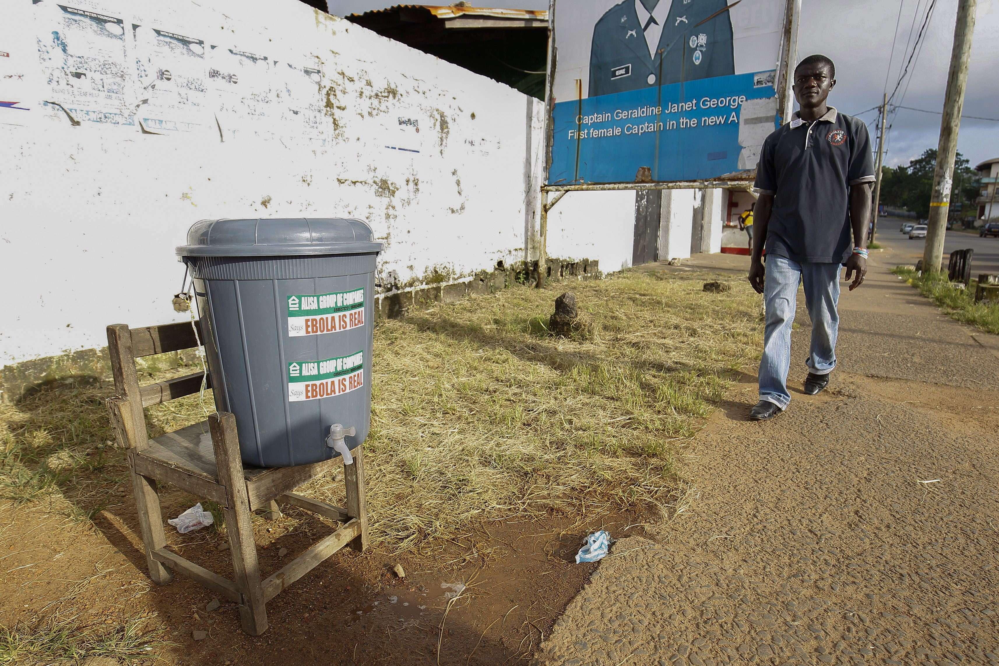 Un hombre camina frente a un balde que contiene agua clorinada como medida para contener la propagación del ébola en una calle en Monrovia, Liberia. Foto: EFE en español