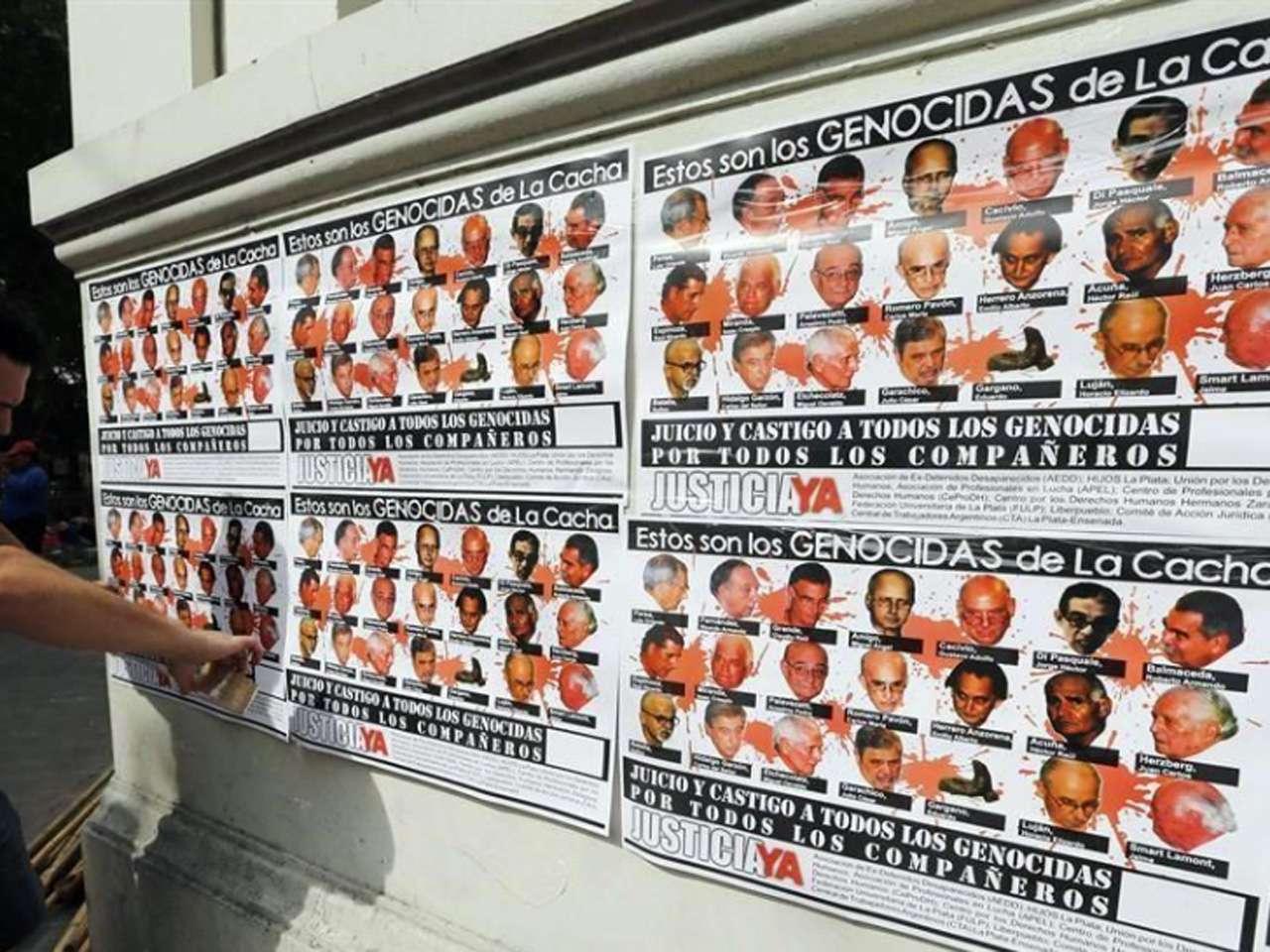 Un hombre pega carteles con con las caras de aquellos que cometieron genocidio en el centro de detención clandestino de La Cacha durante la dictadura militar, en La Plata, Argentina Foto: Reuters en español