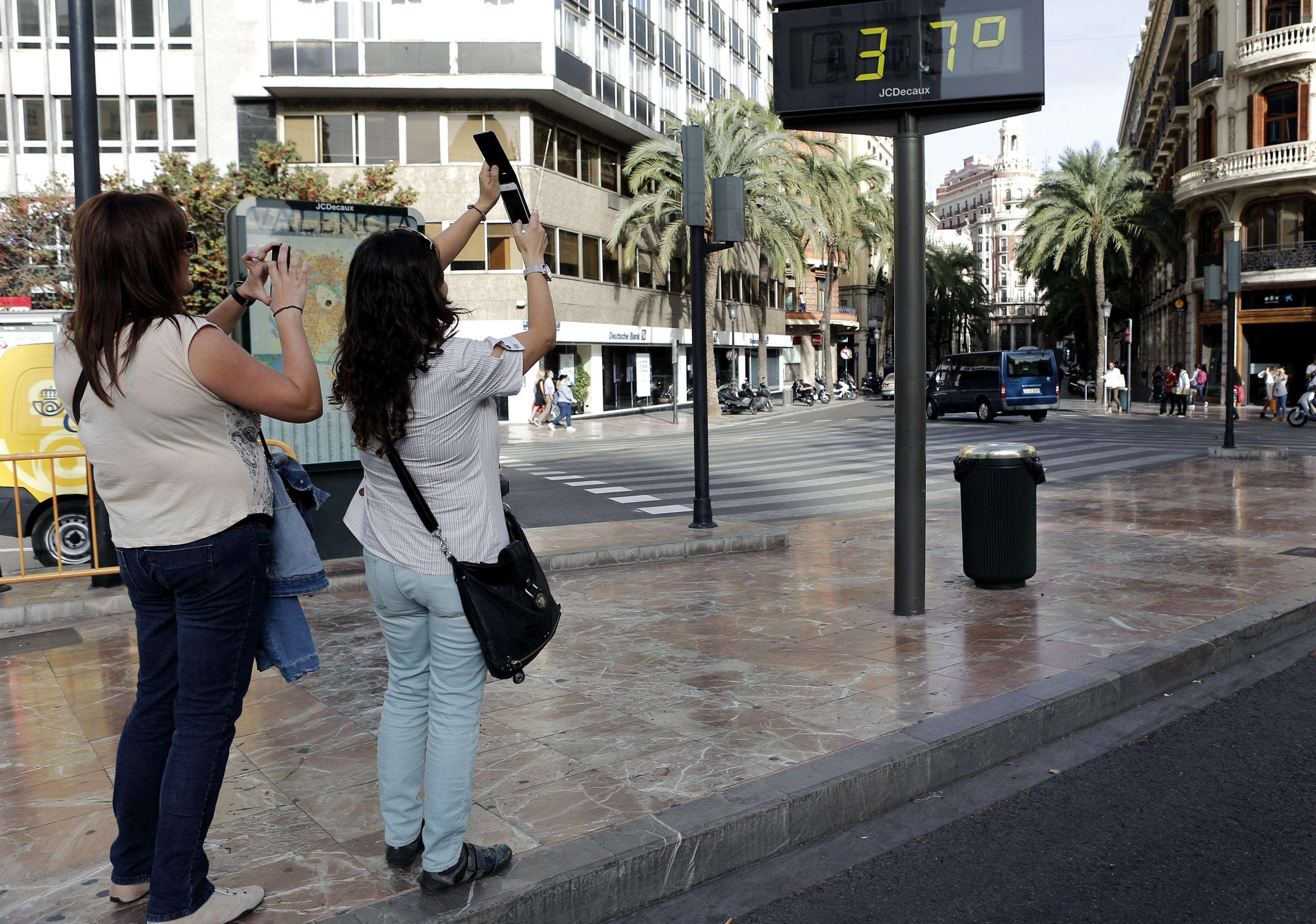 Varias jóvenes fotografían un termómetro que marca 37 grados en el centro de la capital valenciana, el 21 de octubre de 2014. La ciudad de Valencia registró a las 14.30 horas una temperatura de 34,7 grados, el valor más alto registrado en octubre en la ciudad desde 1869, según la Agencia Estatal de Meteorología (Aemet) . Foto: EFE en español