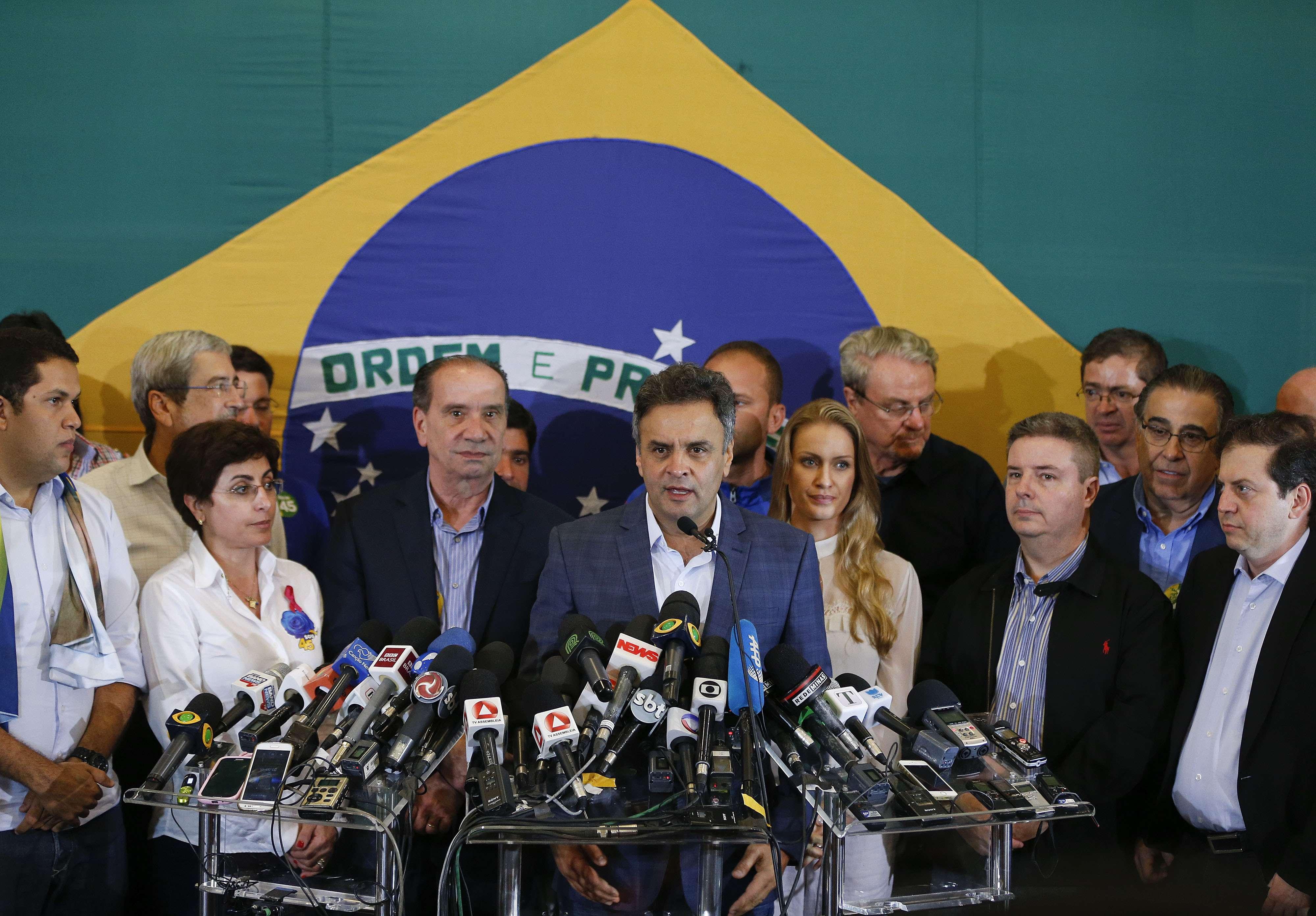 """O candidato a presidente derrotado no segundo turno, Aécio Neves (PSDB), foi recebido antes de seu primeiro discurso após a divulgação do resultado sob os gritos de """"Aécio guerreiro, orghulho brasileiro"""". Ele afirmou que ligou para a presidente reeleita, Dilma Rousseff (PT), lhe desejou sucesso e lhe disse que """"a maior de todas as prioridades deve ser unir o Brasil em torno de um projeto honrado e que dignifique a todos os brasileiros"""". Foto: Andre Penner/AP"""