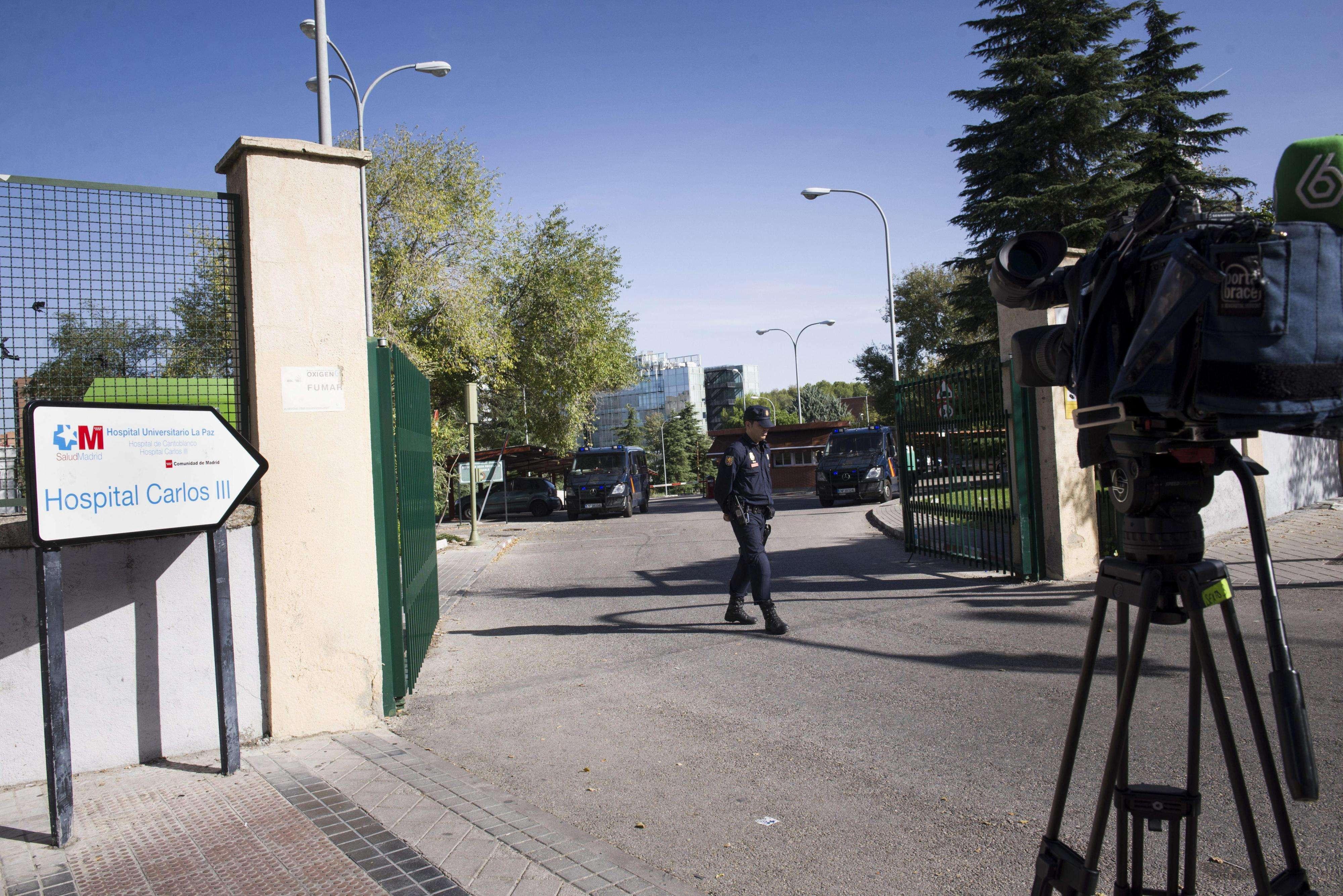 Un agente de la Policía Nacional y algunos medios de comunicación a las puertas del Hospital Carlos III de Madrid, donde continúa ingresada Teresa Romero, la auxiliar de enfermería curada de ébola. Foto: EFE en español