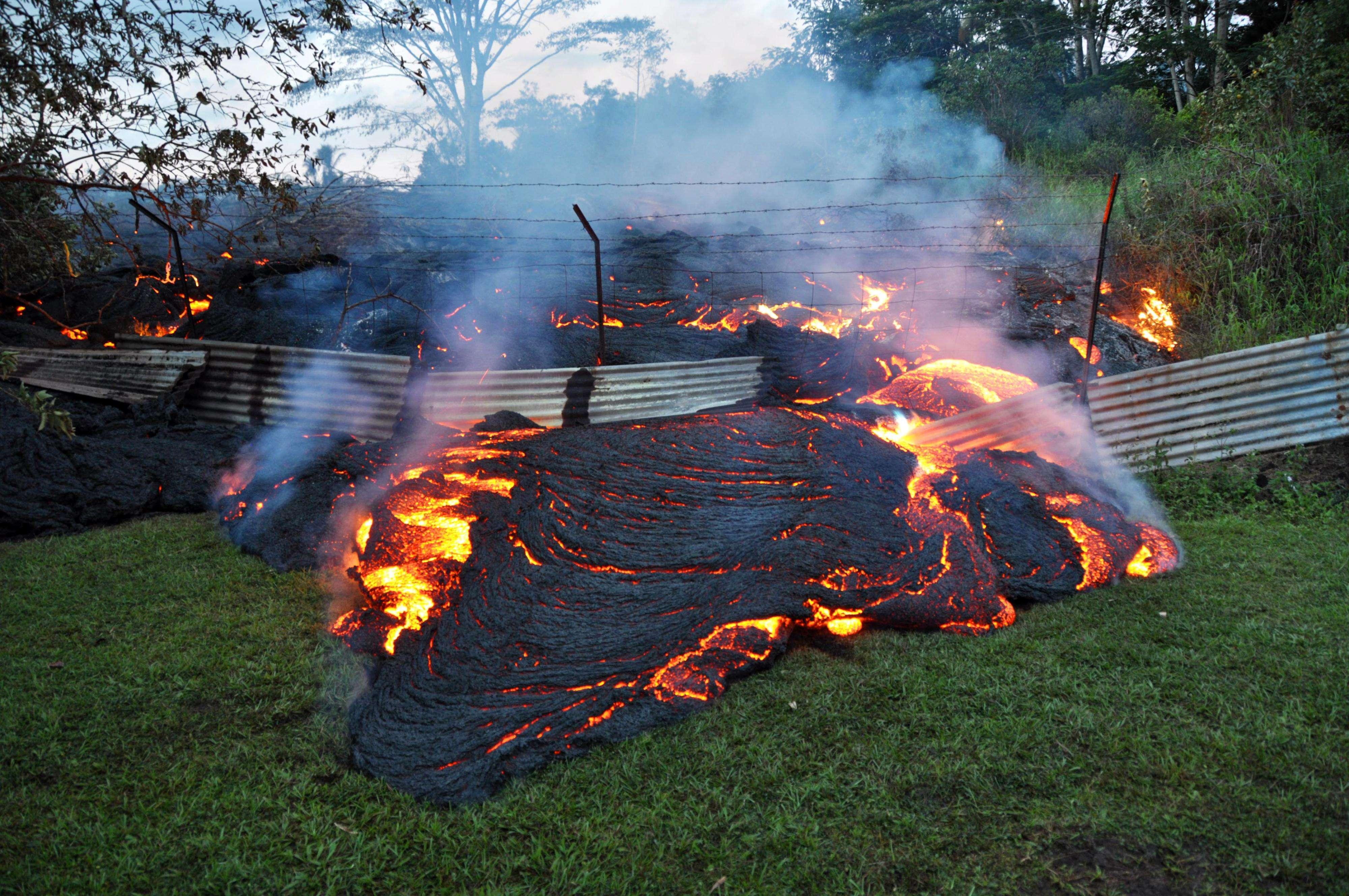 La lava atraviesa una cerca que limitaba una finca en Pahoa, en la Gran Isla de Hawai. Foto: AP en español