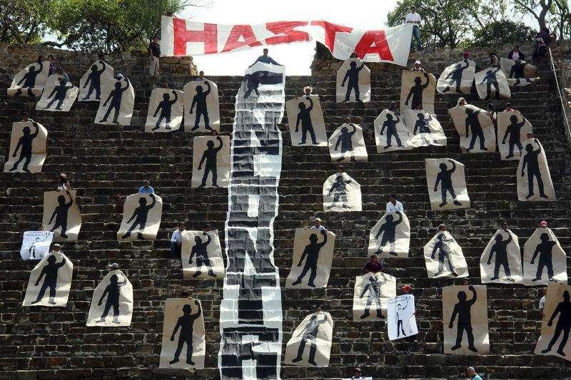 Ativista de uma organização chamada Comuna fazem protesto em que seguram silhuetas representando 43 estudantes desaparecidos no México, no sítio arqueológico de Monte Alban, em Oaxaca. 12/11/2014. Foto: Jorge Luis Plata/Reuters