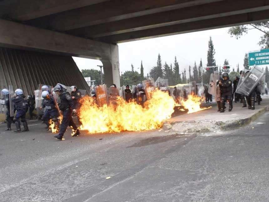 El uniforme de un agente se prendió a raíz del fuego. Se reportaron algunos policías heridos tras el enfrentamiento. Foto: Quadratín México. Foto: Quadratín México