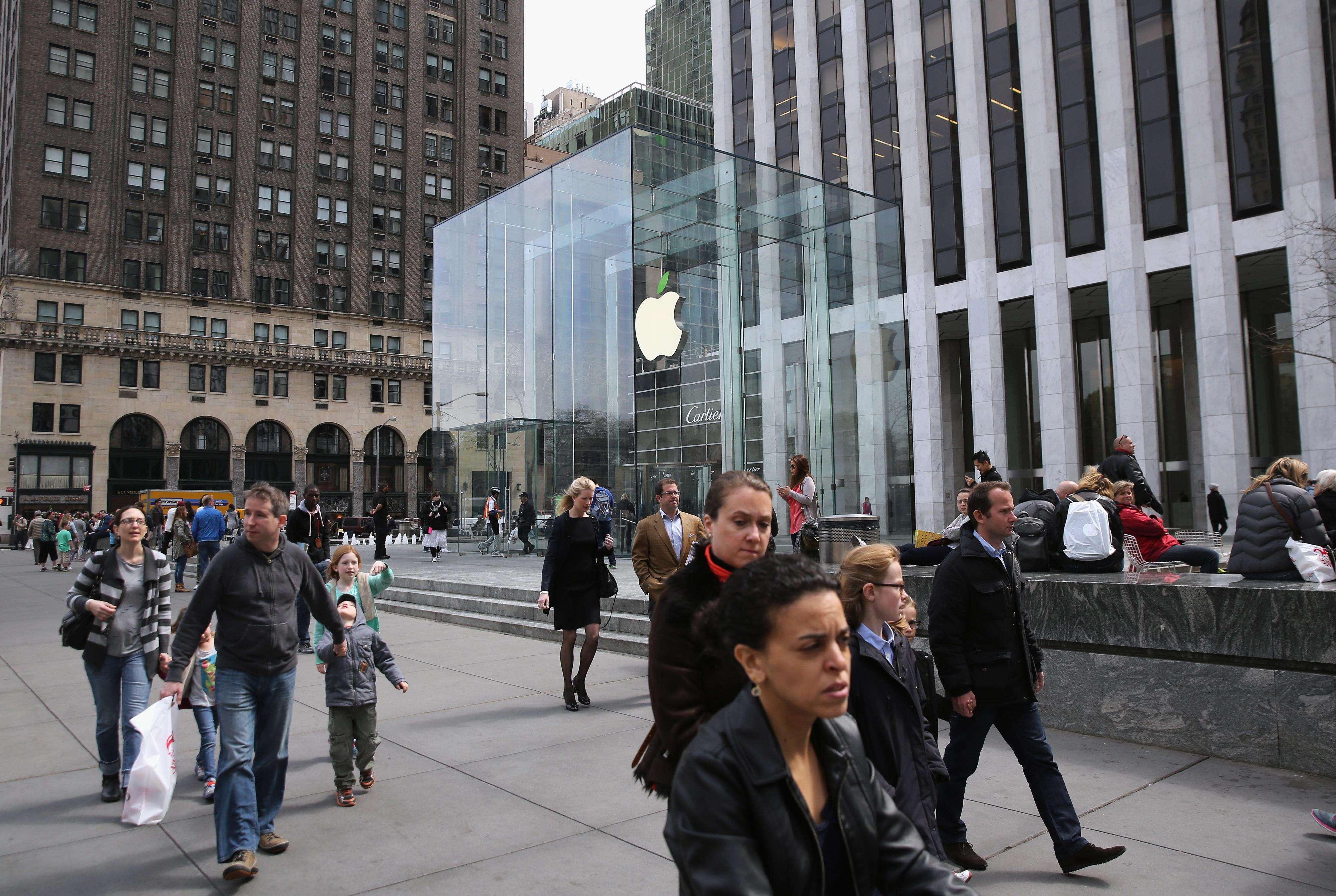 Algunas personas pasan por la tienda Apple localizada en la Quinta Avenida de NY. Foto: Getty Images