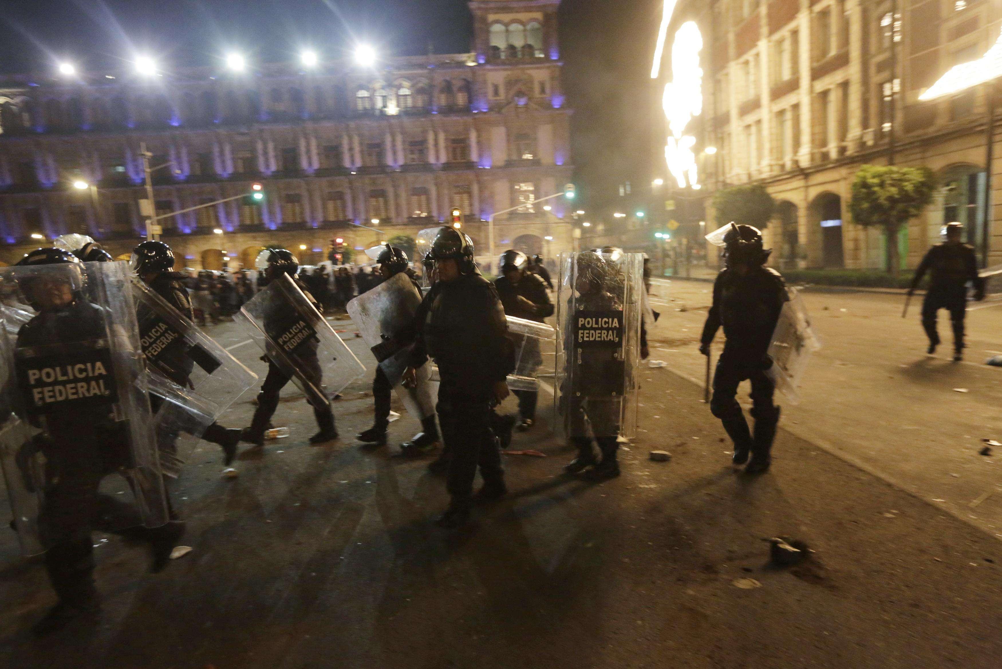 Grupos de manifestantes chocaron con policías antidisturbios en el histórico centro de Ciudad de México, al final de una marcha masiva para protestar por la desaparición de 43 estudiantes que ha causado indignación en un país golpeado por la violencia del narcotráfico. En la imagen, antidisturbios en el Zócalo en México DF el 20 de noviembre de 2014. Foto: Reuters en español