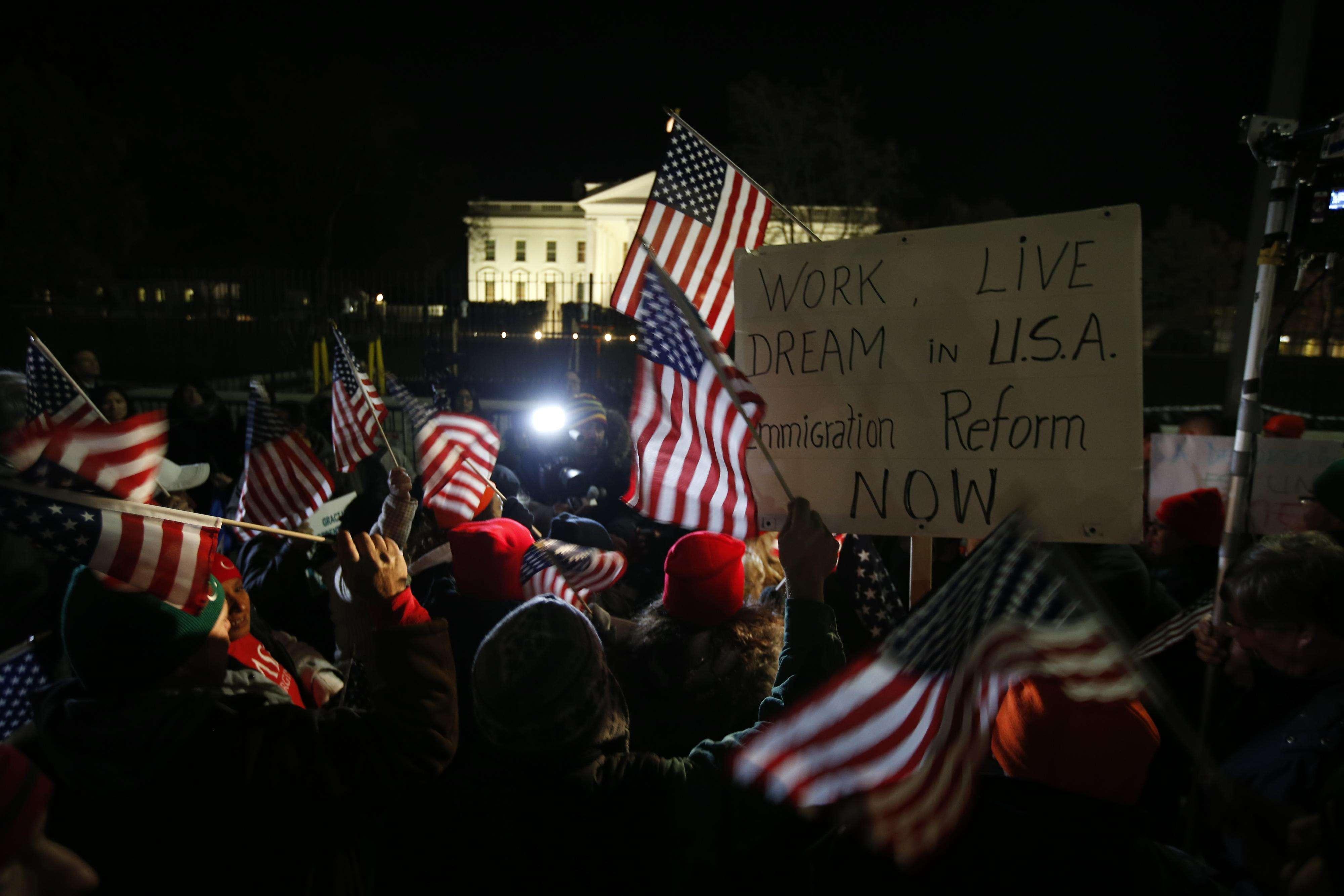 Participantes en un mitin levantan carteles y hacen ondear banderas estadounidenses mientras se reúnen frente a la Casa Blanca, en Washington,el jueves 20 de noviembre de 2014 Foto: AP en español