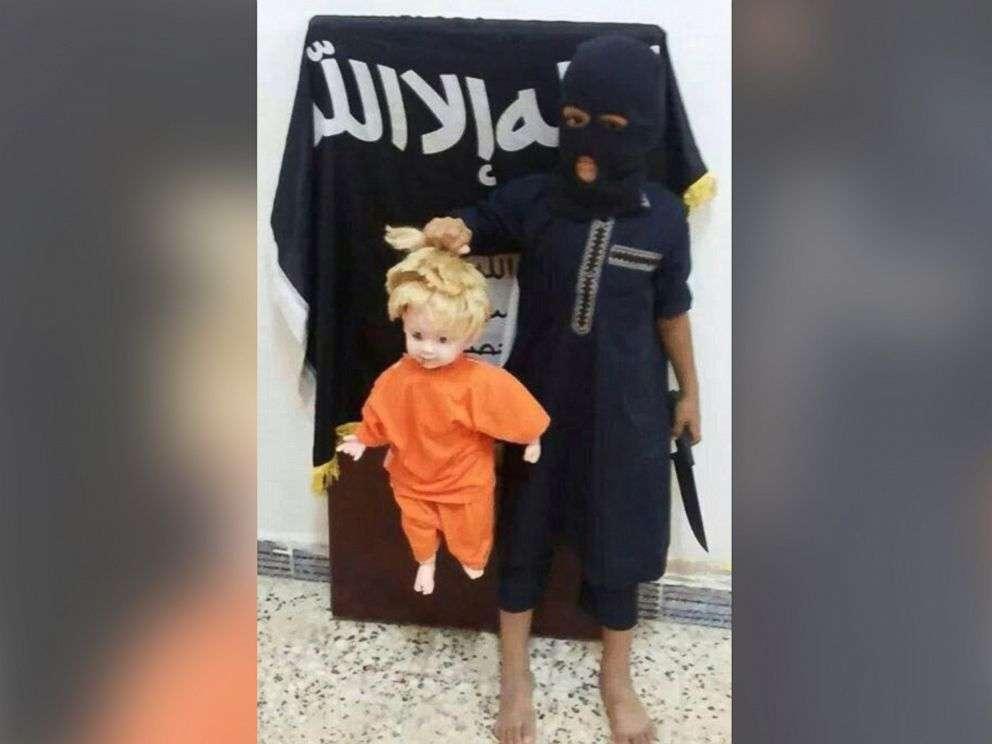 """Crianças são """"ensinadas"""" a segurar cabeças de vítimas e, em novo vídeo, aparecem manejando armas Foto: The Trend Online/Reprodução"""