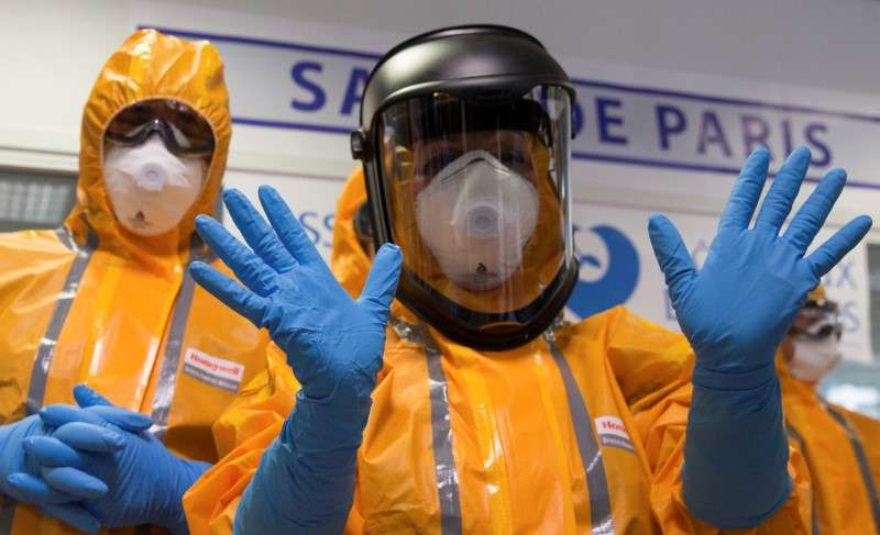Funcionário do hospital francês, Necker, mostra luvas e roupas de proteção usadas para tratamento de paciente - que não teve nome e nacionalidade divulgados Foto: Philippe Wojazer/Reuters