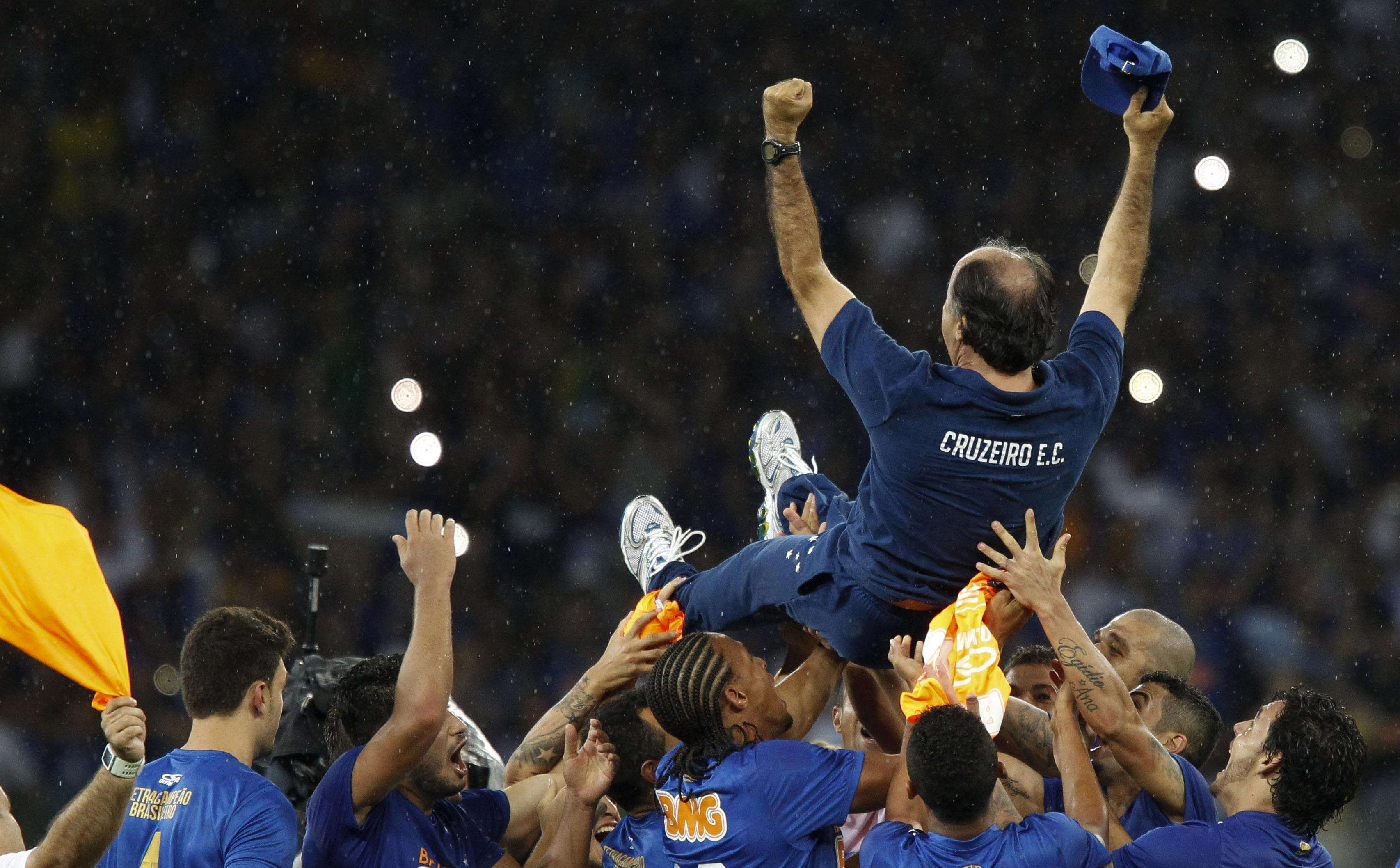 Cruzeiro's players toss their head coach Marcelo Oliveira (top) as they celebrate after winning the Brazilian Serie A championship title with three matches to spare, with a 2-1 win over Goias soccer club, in Belo Horizonte November 23, 2014. Cruzeiro were crowned Brazilian league champions for the second consecutive year on Sunday after they beat Goias 2-1 at home to open up an unbeatable lead at the top of Serie A. REUTERS/Washington Alves (BRAZIL - Tags: SPORT SOCCER) Foto: STRINGER/BRAZIL/REUTERS