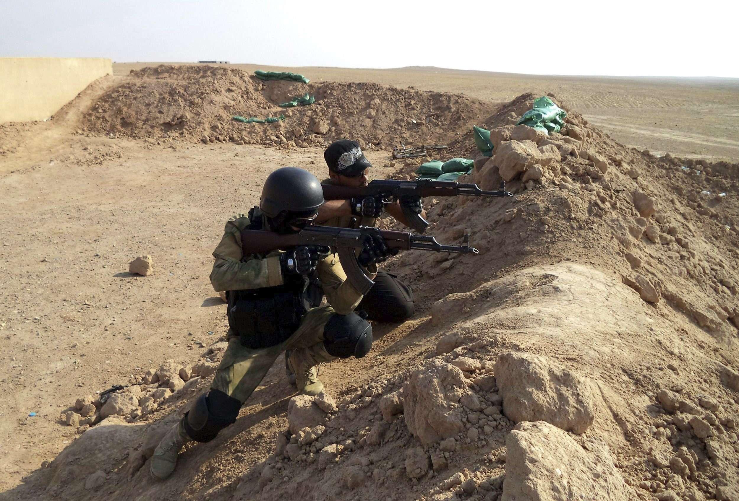 Fotografía facilitada el 21 de noviembre que muestra a dos miembros de la milicia iraquí chií al-Abbas, que lucha junto a las fuerzas iraquíes para combatir contra el grupo yihadista Estado Islámico (EI), mientras toman posiciones en Tikrit, Irak, el 20 de noviembre de 2014. Foto: EFE en español