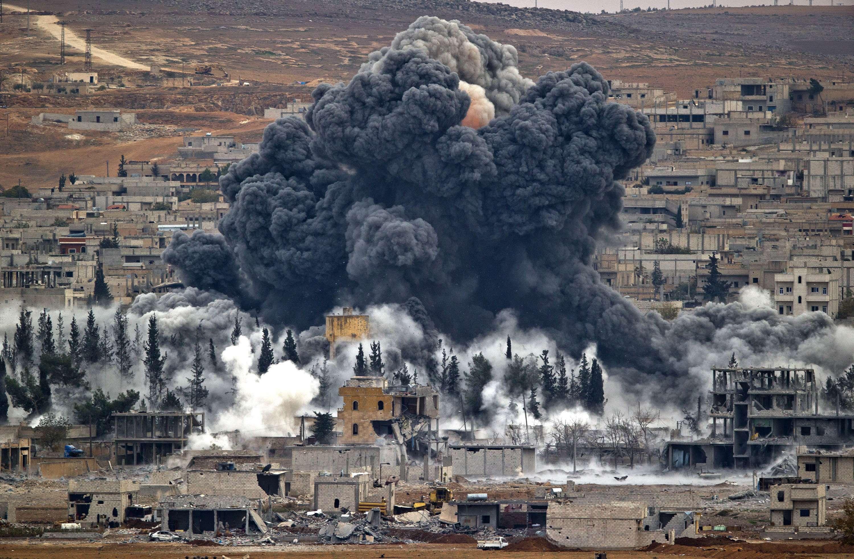 En esta foto de archivo del 17 de noviembre de 2014 se ve una nube que se alza de la ciudad siria de Kobani tras un ataque aéreo de EEUU, visto desde Suruc, en el lado turco de la frontera. Foto: AP en español
