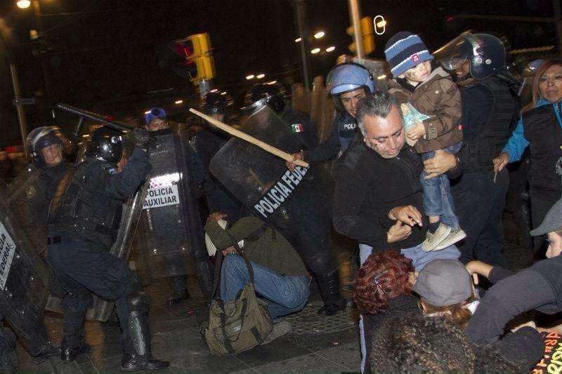 20 de noviembre.- Tras concluir las marchas en apoyo a Ayotzinapa, policías federales avanzaron hacia la Plaza de la Constitución, empujando a los asistentes hacia las calles aledañas al zócalo capitalino. Durante esta acción, los policías utilizaron sus toletes y escudos para empujar y golpear a los ciudadanos que encontraban a su paso, sin importar el género o edad de la persona. Estas agresiones arbitrarias fueron registradas en imágenes y publicadas en las redes sociales. Foto: Imagen tomada de Twitter