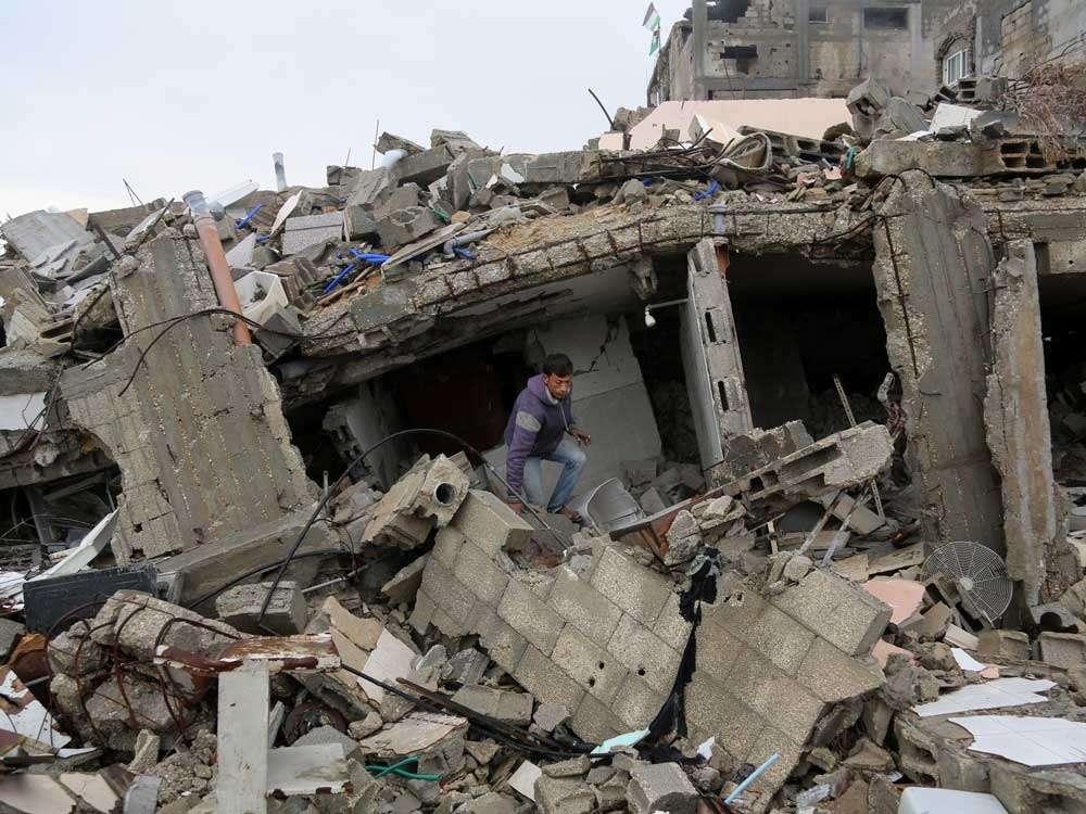 Un palestino camina entre los escombros de su casa, destruida durante el reciente conflicto entre Israel y Hamas en Shijaiyah, en Gaza. Foto: AP en español
