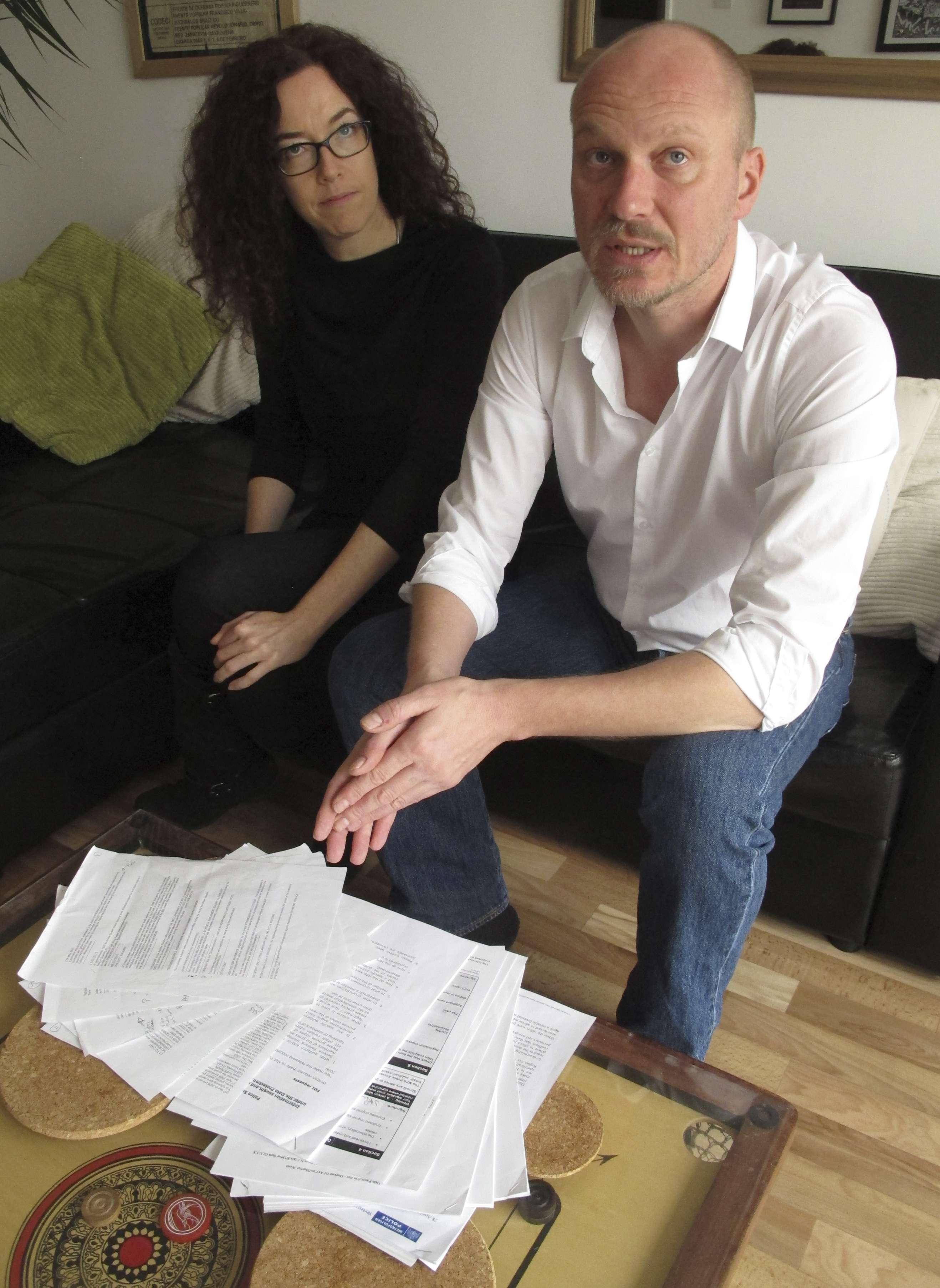 El video reportero Jason Parkinson, de 44 años, y la fotoperiodista Jess Hurd, de 41 años, muestran los documentos que demuestran la vigilancia policial de la que fueron objetos, en su casa de Londres, 21 de noviembre de 2014. La pareja pertenece al grupo de seis periodistas que demandaron al gobierno británico por espiarlos. Foto: AP en español