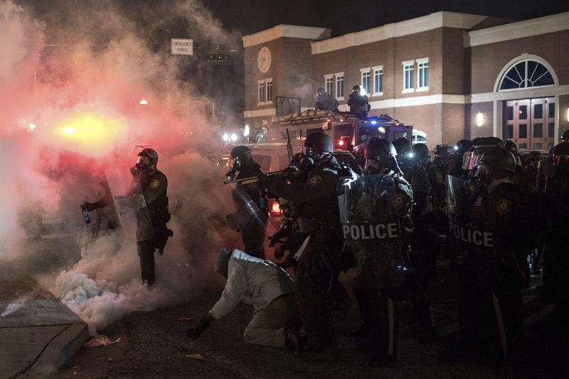 Manifestantes y policías se enfrentan durante unos disturbios tras conocer el fallo de un gran jurado que ha decidido no imputar al policía Darren Wilson por la muerte del joven Michael Brown. Foto: EFE en español