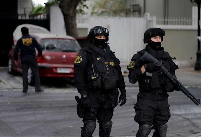 Dos funcionarios de la PDI estuvieron resguardando el lugar donde un auto resultó quemado tras recibir una bomba molotov en el Cuartel de la Policía de Investigaciones ubicado en calle Condell, tras un atentado además a dicho lugar. Foto: Agencia UNO