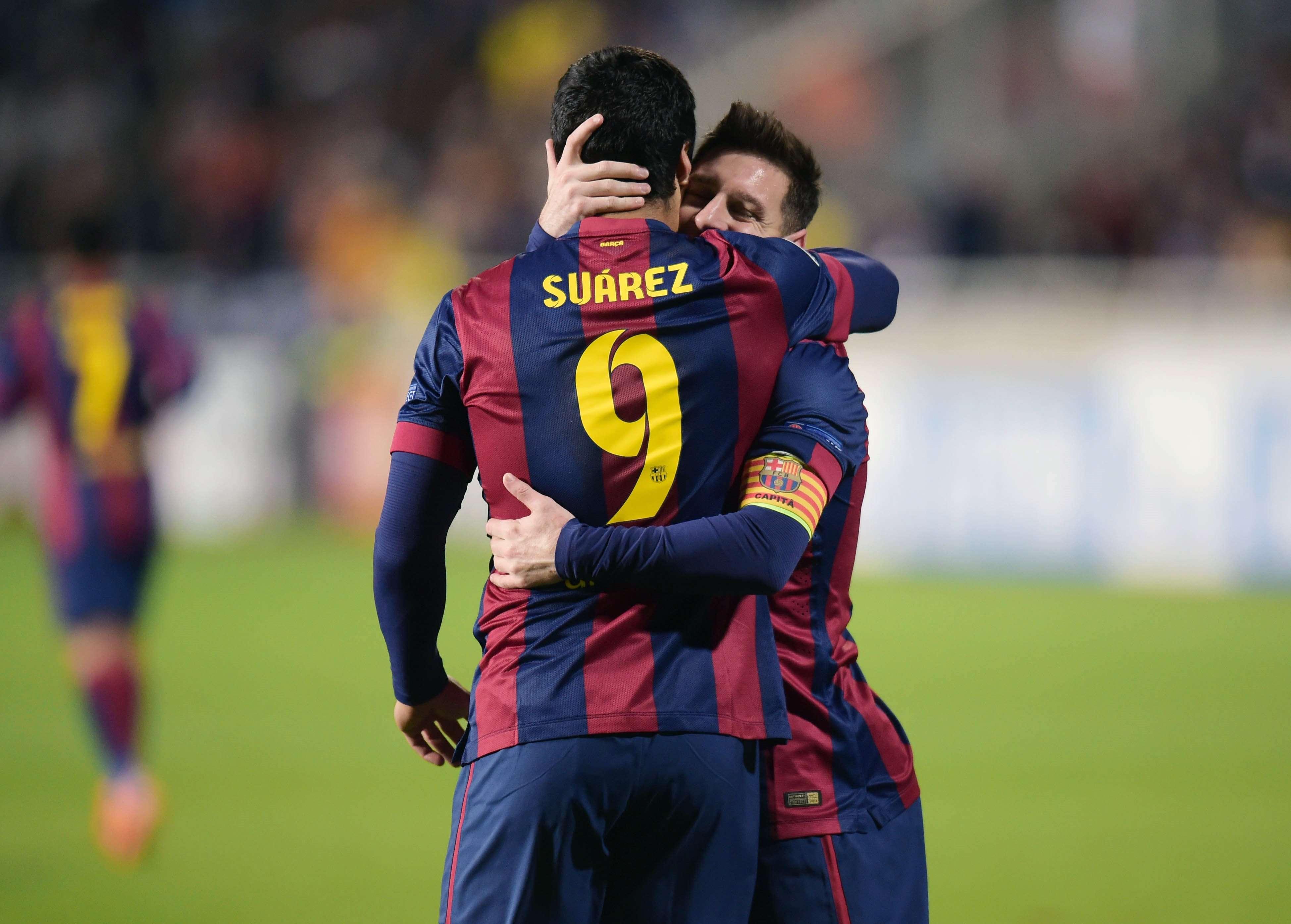 Suárez e Messi se abraçam em comemoração de gol Foto: Andreas Manolis/Reuters