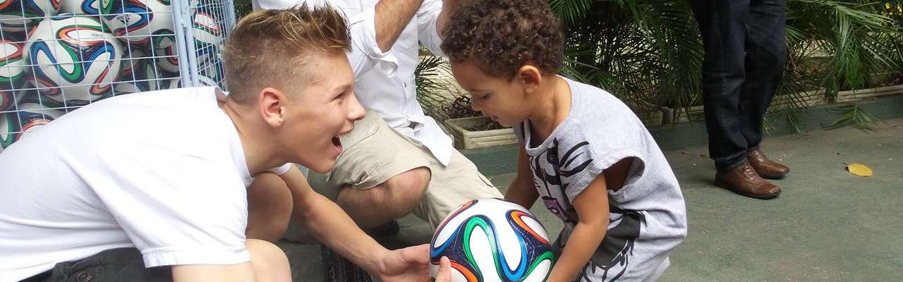 Ethan King entrega a bola para uma criança carente no Rio de Janeiro. Conheça sua história de vida Foto: André Naddeo / Terra