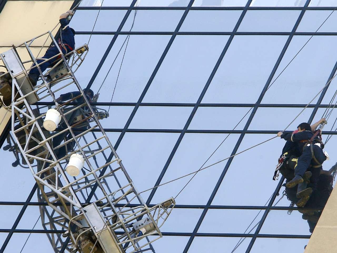 Un equipo de bomberos rescató hoy a dos trabajadores que pasaron una hora colgados a unos 70 metros de altura en la fachada de un céntrico hotel en Santiago de Chile, después de que cediera el andamio que los sujetaba mientras limpiaban los cristales. Foto: EFE en español