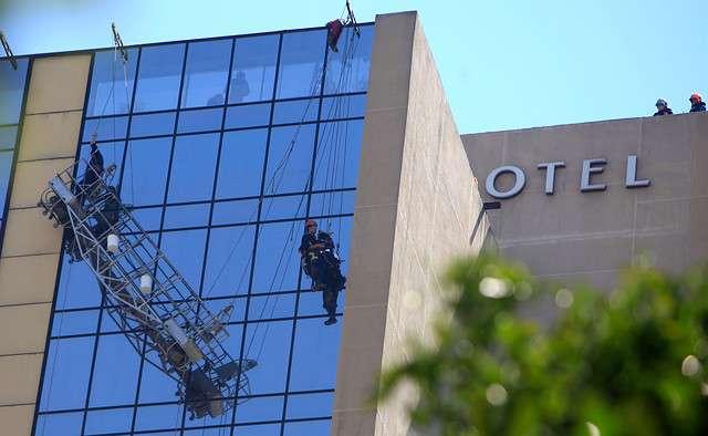 Rescatan a dos trabajadores que se encontraban limpiando los vidrios en el Hotel Crowne Plaza. Foto: Agencia Uno