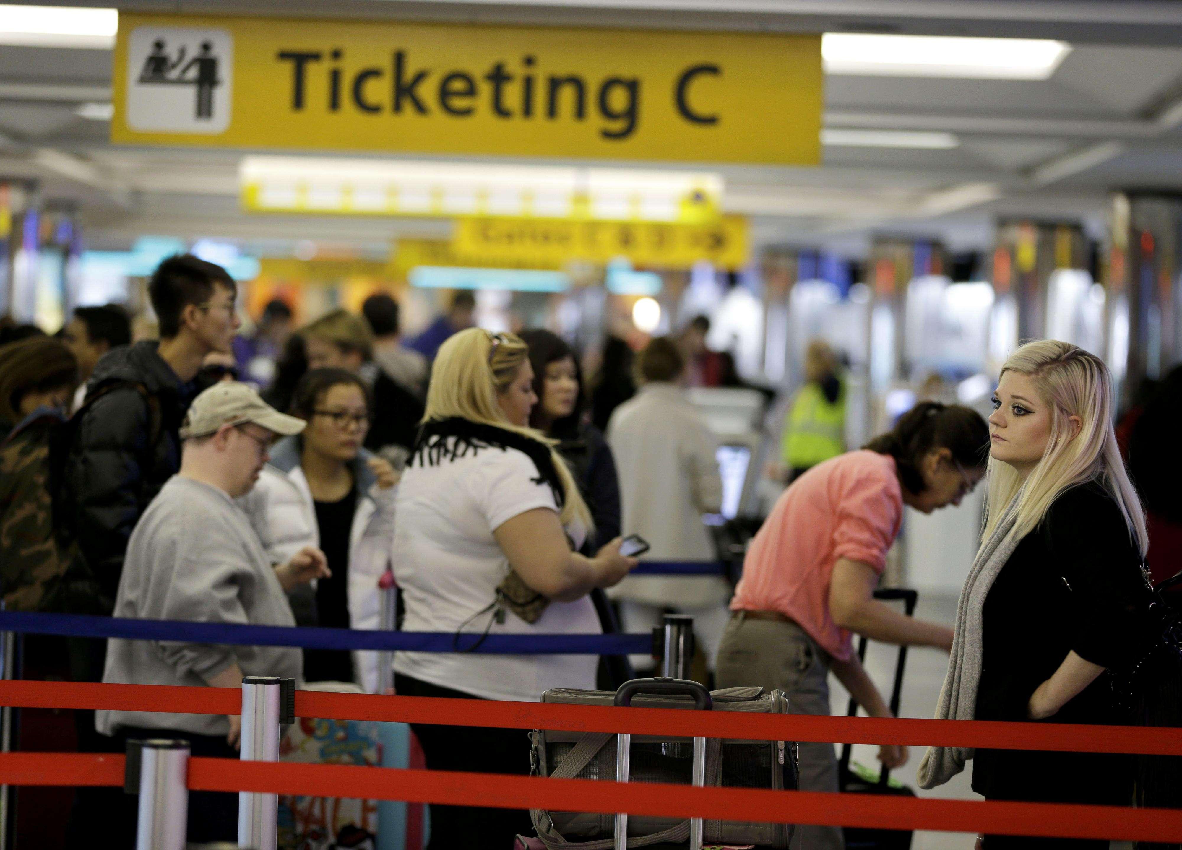 Viajeros hacen fila mientras esperan para embarcar en el aeropuerto de LaGuardia, en Nueva York, el 25 de noviembre de 2014, en los días previos al feriado de Acción de Gracias.( Foto: AP en español