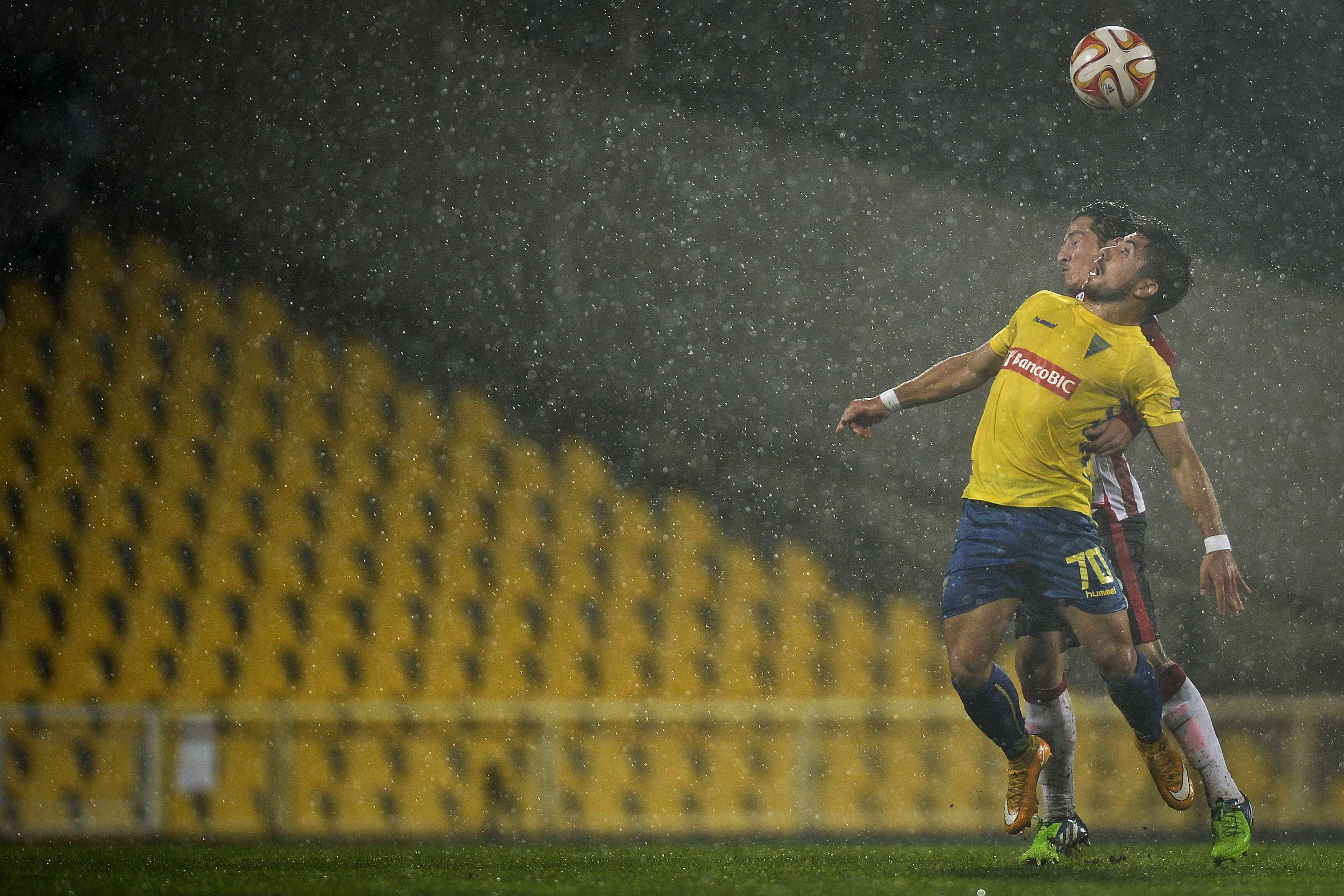 Guardado marca a Toze bajo la intensa lluvia. Foto: AFP