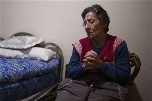 Carmen Martinez Ayudo, 85-years old, prays during her eviction in Madrid, Spain, Friday, Nov. 21, 2014. Rayo Vallecano, the Spanish first division soccer team said Thursday Nov. 27, 2014, it has opened a bank account to collect donations for Carmen Martinez Ayudo whose eviction last week sparked an outcry. Martinez was evicted from the apartment she owned and lived in for decades in Madrid's working-class neighborhood of Vallecas. Her son had used it as collateral for a 40,000-euro ($50,000) loan and could not make payments after losing his job. (AP Photo/Andres Kudacki) Foto: AP en español