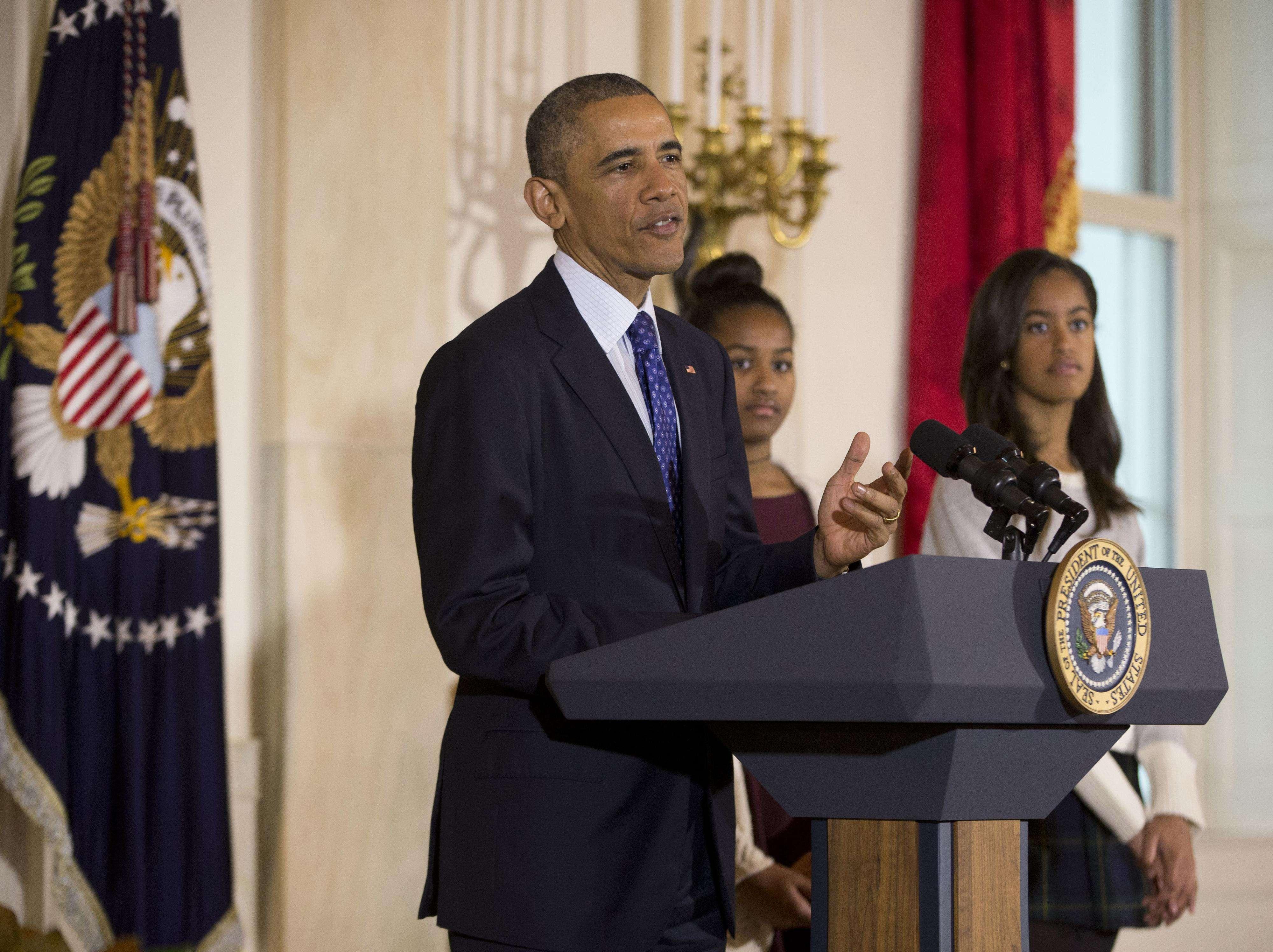 El presidente Obama acompañado de sus hijas Sasha y Malia durante el tradicional indulto a los pavos, en la Casa Blanca, este miércoles de noviembre del 2014. Foto: AP en español