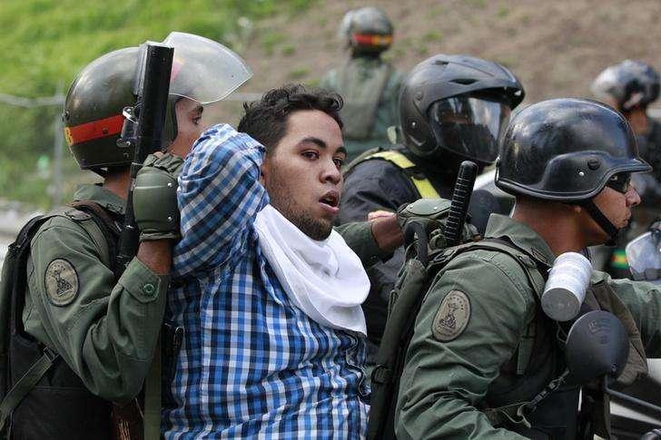 """Imagen de archivo de policías venezolanos detienendo a un manifestante durante una protesta contra el gobierno de Nicolás Maduro en Caracas. 04 junio, 2014. El comité de las Naciones Unidas contra la tortura expresó el viernes su """"alarma"""" por las denuncias de tortura y malos tratos de parte de las autoridades venezolanas durante los meses de protestas opositoras a principios de este año, e instó al país a investigar a fondo los incidentes. Foto: Christian Veron/Reuters"""
