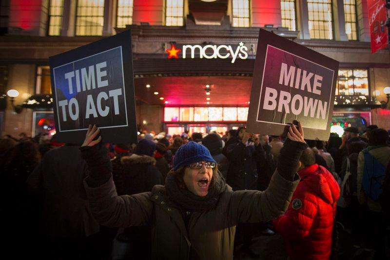 Manifestantes ergue cartazes de protesto em frente a uma loja da rede Macy's, em Nova York. 27/11/2014. Foto: Andrew Kelly/Reuters