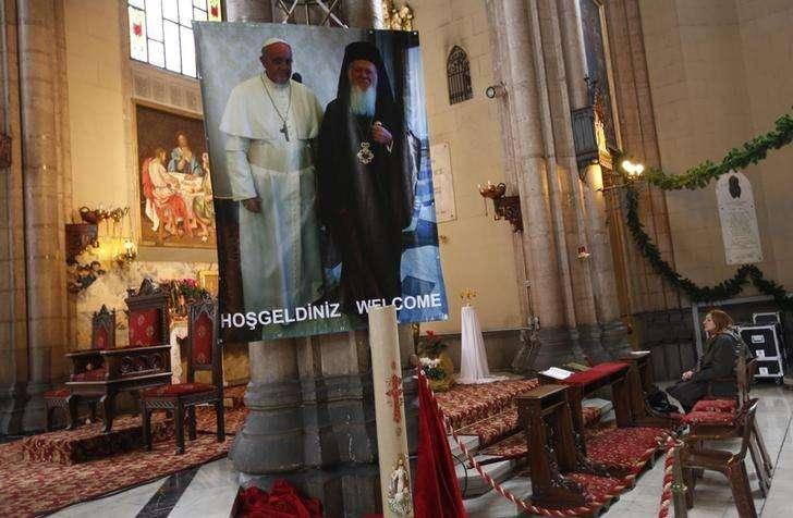 Mulher reza perto de cartaz com fotos do papa Francisco e do patricarca Bartolomeu em igreja católica no centro de Istambul. 28/11/2014 Foto: Murad Sezer/Reuters
