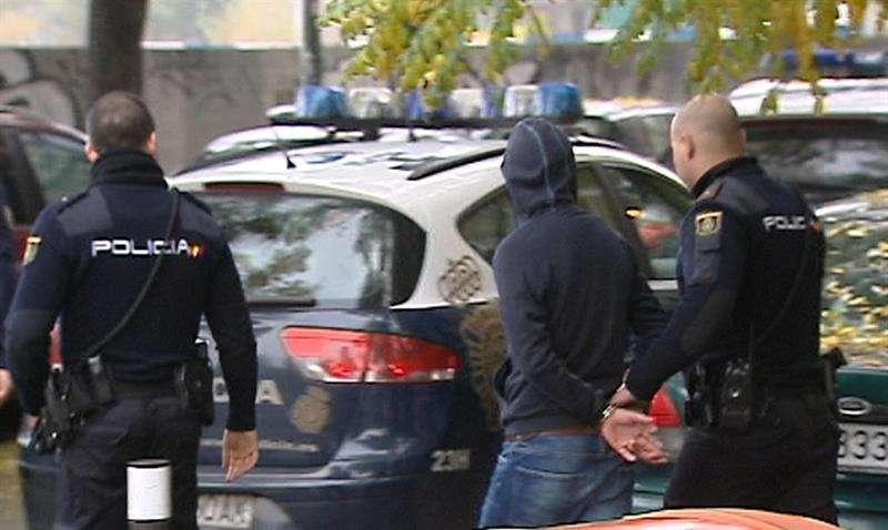 Imagen de televisión de efectivos de la Policía Nacional que conducen a uno de los quince detenidos en la reyerta en Madrid Río producida entre radicales del Deportivo de La Coruña y del Atlético Foto: EFE