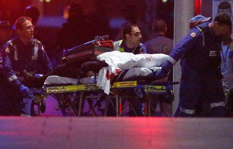 Paramédico retiram pessoa coberta por cobertor manchado de sangue do café Lindt em Sydney, na Austrália. 15/12/2014 Foto: David Gray/Reuters
