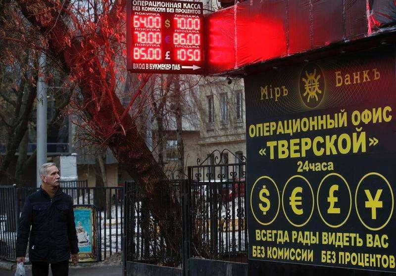 La fuerte subida de los tipos de interés que llevó a cabo el lunes el banco central ruso no lograba aliviar la presión sobre el rublo el martes, dado que el mercado seguía poniendo a prueba la resolución del organismo para defender a la moneda y presionaba a la debilitada economía rusa. En la imagen, un hombre pasa junto a un edificio con una oficina de cambio en Moscú, el 16 de diciembre de 2014. Foto: Maxim Zmeyev/Reuters