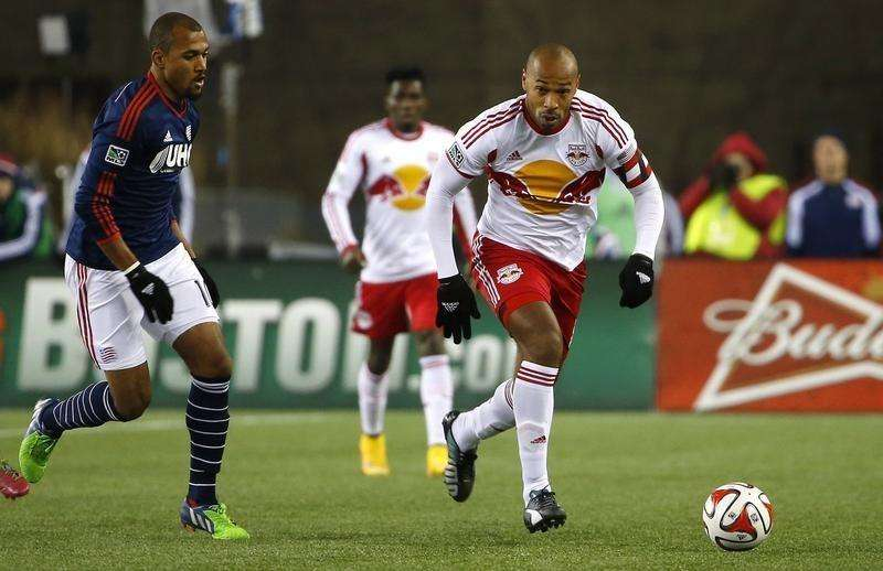 New York Red Bulls forward Thierry Henry (14) carries the ball past New England Revolution forward Teal Bunbury (10) during the second half of the Eastern Conference Championship at Gillette Stadium. Mandatory Credit: Winslow Townson-USA TODAY Sports. Foto: Reuters