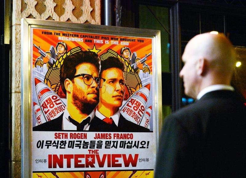 """Segurança na entrada de um cinema em frente ao pôster do filme """"A Entrevista"""", em Los Angeles. 11/12/2014 Foto: Kevork Djansezian/Reuters"""