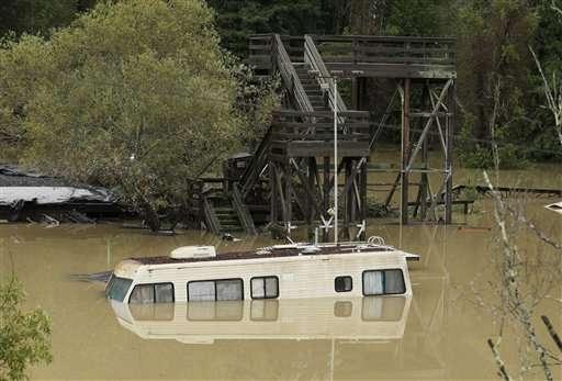 Una casa rodante está casi cubierta de agua a causa del desbordamiento del río Russian por las lluvias en Guerneville, California, el 12 de diciembre de 2014. Foto: AP en español