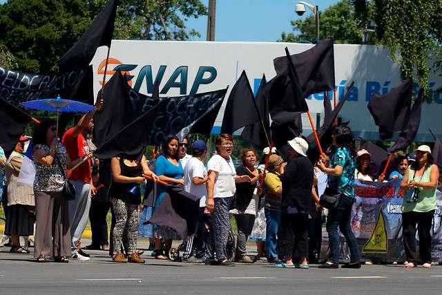 Una manifestación en la puerta de ENAP-Refineria Bíobio, realizaron los vecinos del sector El Triangulo de Hualpén por el quiebre de la mesa de negociación entre los pobladores de El Triángulo y la estatal ENAP, luego de los últimos eventos de malos olores que afectaron a los residentes del sector. La mesa de negociación buscaba la relocalización de las familias más afectadas. No obstante, ENAP insiste en no establecer una cláusula que deje en libertad a los vecinos de El Triángulo de iniciar acciones indemnizatorias. La estatal pretende dejar establecido que la relocalización es el pago de todo el daño causado, y considerando que este proceso puede tardar entre 3 a 5 años, más los reiterados episodios de malos olores, los vecinos no aceptaron. Foto: Agencia UNO