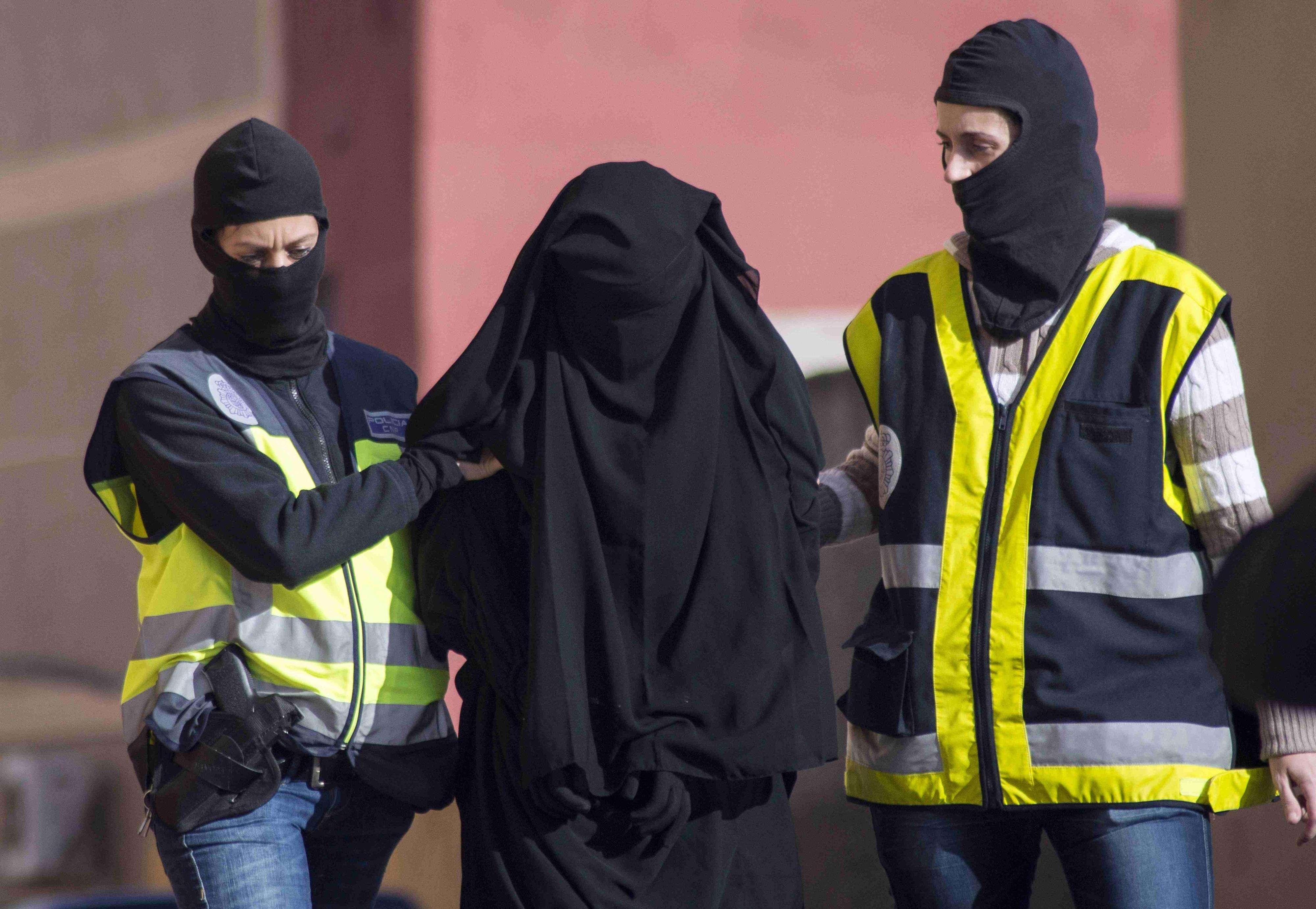 Policiais mascarados espanhóis prendem uma mulher suspeita de participar de uma organização que recrutava mulheres para os jihadistas do Estado Islâmico Foto: Jesus Blasco de Avellaneda/Reuters