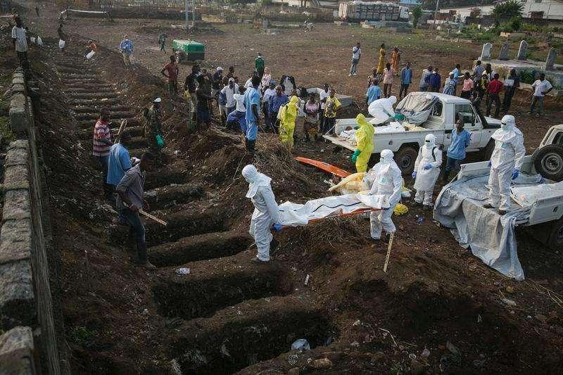 Profissionais de saúde enterram corpo de vítima de Ebola em Freetown. 17/12/2014 Foto: Baz Ratner/Reuters