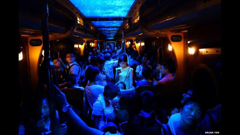 A foto de uma mulher iluminada pelo brilho de seu celular em um trem lotado venceu o prêmio principal em um concurso anual de fotografia da National Geographic Foto: BBCBrasil.com
