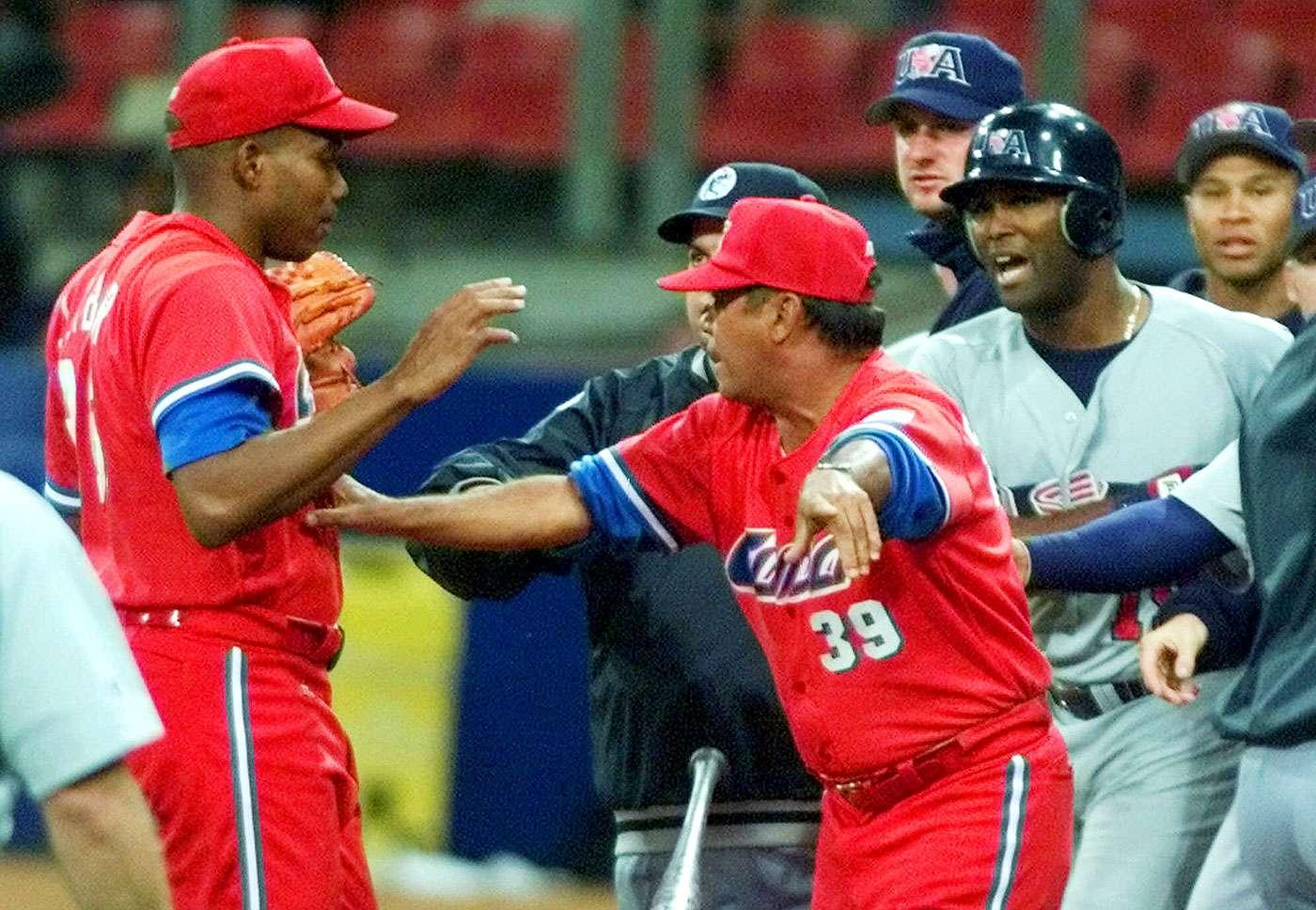 En imagen del 23 de septiembre de 2000, el manager de la selección de Cuba, Servio Borges (39), separa al pitcher José Ibar, izquierda, y al bateador estadounidense Ernie Young luego que Ibar dio un pelotazo a Young en el cuarto inning durante los Juegos Olímpicos Sydney 2000. Foto: Eric Gay/AP
